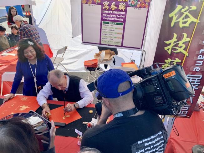 年節展吸引主流電視台報導,圖為ABC 7記者拍攝寫書法畫面。(記者陳開╱攝影)