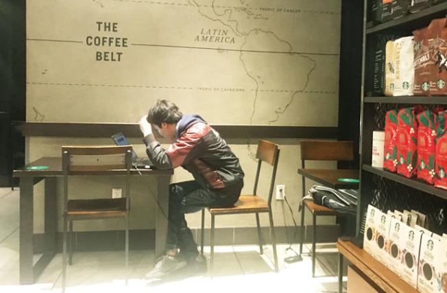 一名華裔男子正在咖啡店內埋首看電腦,遇劫的華裔男子坐在他背後的座位。(記者李秀蘭/攝影)