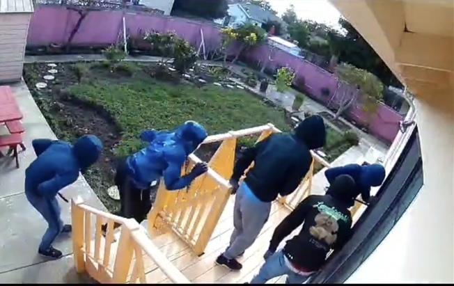 五名蒙面及拉上帽子的非裔男子利用撬棒,從後園打開東灣聖利安住市一個亞裔住宅的大門。(取材自YouTube)