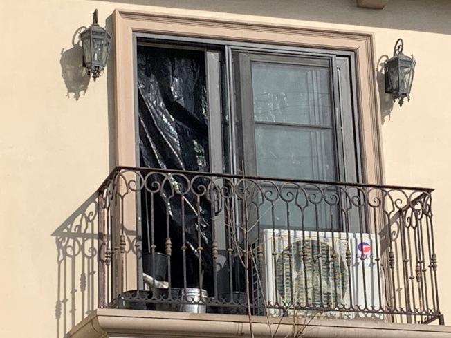 二樓的窗戶被打開,露出裡面用於遮光的黑色塑膠袋。(本報記者/攝影)