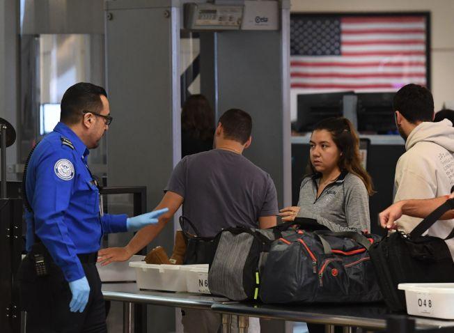 洛杉磯國際機場安檢人員正在檢查旅客行李。(Getty Images)