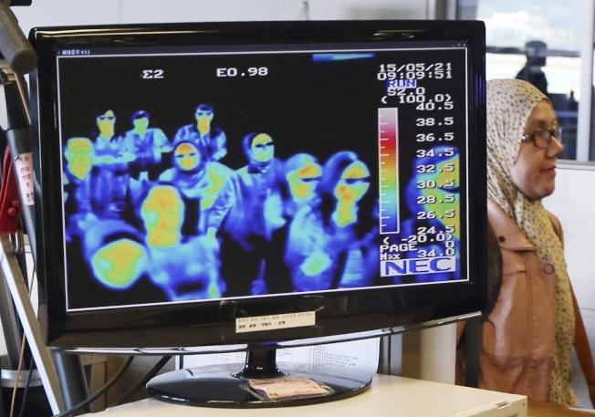 武漢爆發新型冠狀病毒肺炎病例後,中國及鄰國已加強檢疫,圖為南韓機場篩查從中國入境旅客。(美聯社)