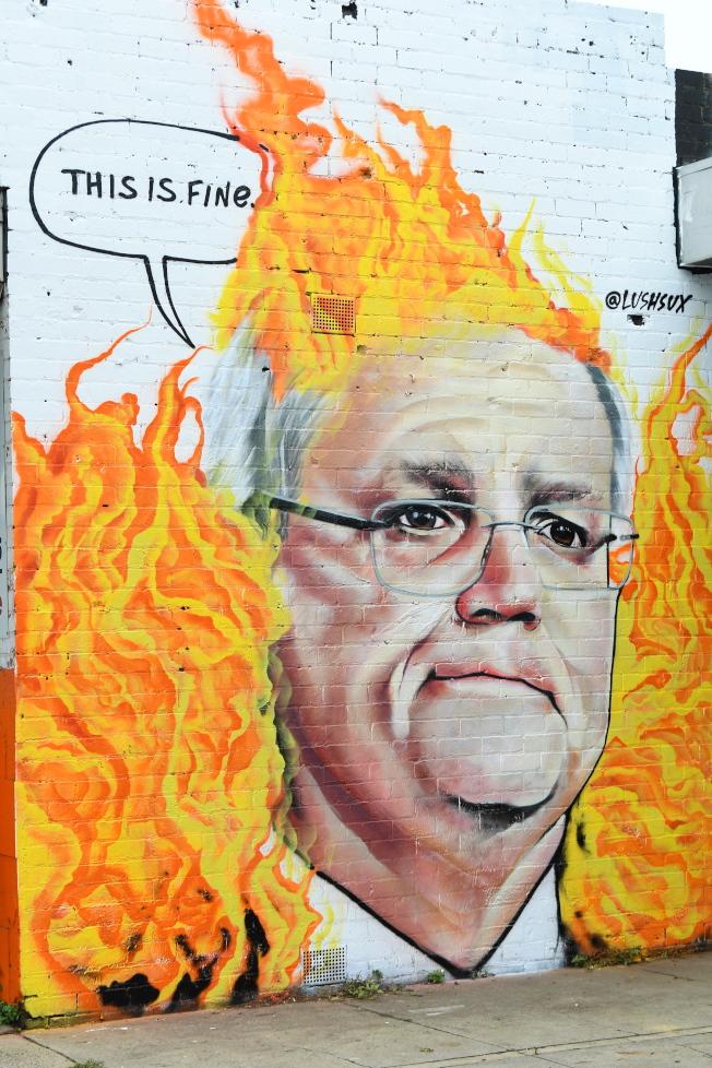 澳洲墨爾本街頭出現諷刺莫里森處理野火不力的壁畫。(歐新社)