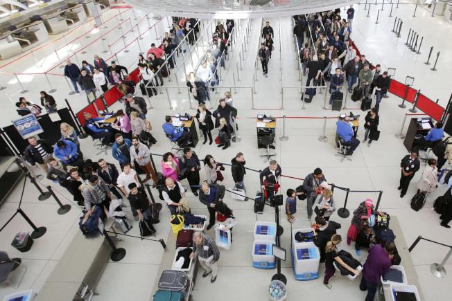 美國為防堵新型冠狀肺炎病毒,在東西岸三大國際機場對武漢來美旅客進行篩檢。圖為甘迺迪機場旅客排隊。(美聯社)