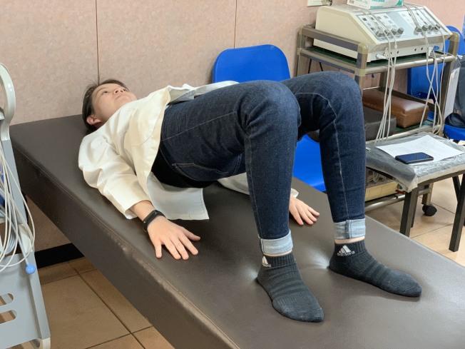 第二招「拱橋運動」,是平躺,屈膝,雙手放置兩側。吸氣,同時以腰部、腹部、背肌力量抬起骨盆與臀部,使臀部抬高離床,讓身體呈一直線,可強化臀部與及下肢肌力的核心肌群訓練,加強脊椎周圍肌肉的支撐力。(記者徐如宜/攝影)