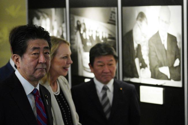日本首相安倍晉三(左)與美國故總統艾森豪的孫女瑪麗(中),19日在東京美日安保條約修訂60周年紀念活動上,參觀一場照片展。(Getty Images)
