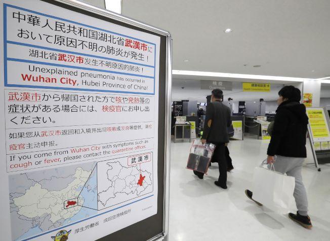 武漢肺炎病例再暴增17例,傳染力不容小覷,也引起國際注意。圖為日本成田國際機場的旅客警示牌,要求來自中國武漢的國際旅客進行篩檢。(Getty Images)