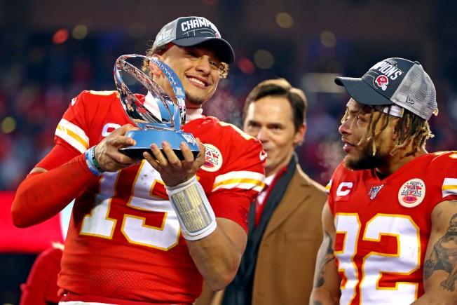 四分衛馬霍姆斯(左)開心舉起美聯冠軍獎盃。(路透社)