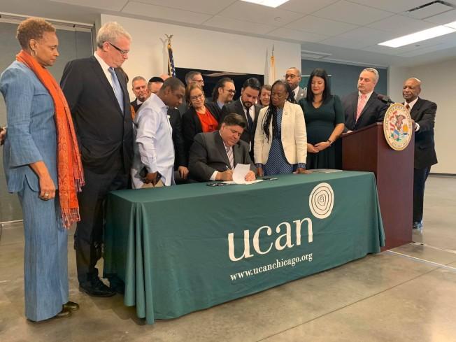 伊州州長普立茲克(圖中坐者)簽署施行「交通罰款免扣駕照」法案,圖右一為主管駕照業務的州務卿懷特。(州長辦公室提供)
