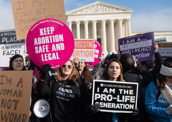 新研究顯示,許多想要墮胎卻被拒絕的婦女都陷入財務困境,而她們和孩子們生活貧困的機率,也比獲准墮胎的婦女更高。圖為支持與反對墮胎權人士在最高法院前抗議。(Getty Images)