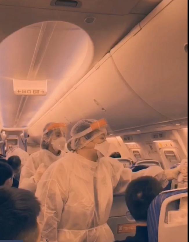 網傳自武漢飛出的航班上,都有穿著防疫裝的醫務人員檢查離境旅客的體溫。(截自視頻)