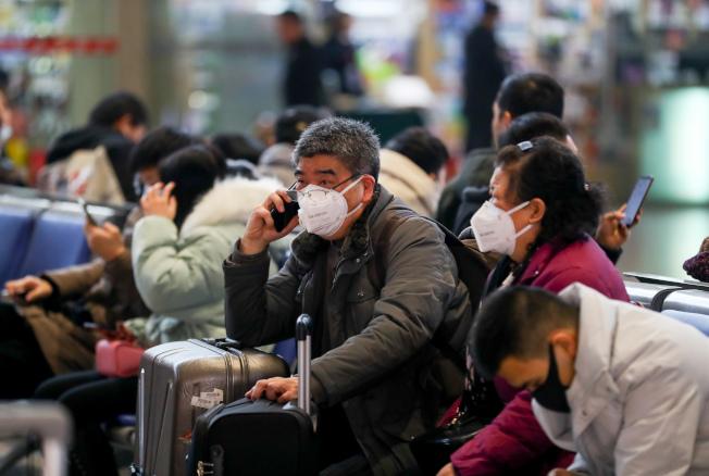 新型冠狀病毒疫情蔓延,21日武漢火車站候車大廳,不少旅客戴著口罩。(中新社)