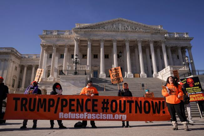 參院如火如荼審理川普總統的彈劾案之際,示威者在國會外面舉牌要求「川普/潘斯下台」。(路透)