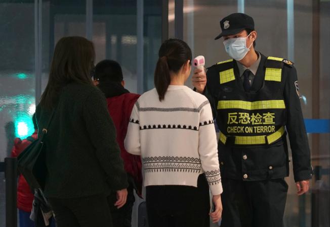 新型冠狀病毒肺炎疫情擴散,重災區湖北武漢已加強管控人員進出。圖為武漢天河機場工作人員為旅客量體溫。(美聯社)