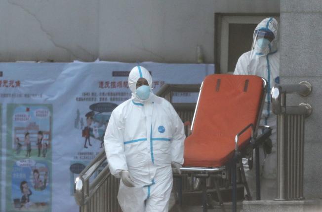 穿著防護服的醫護人員把患者轉到金銀潭醫院集中隔離。(歐新社)