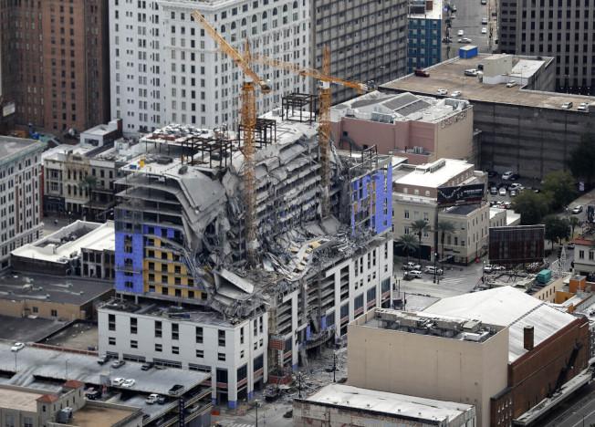 紐奧良市未完工的「硬石飯店」去年10月發生倒塌事故,遮住罹難工人遺體的油布已掉落,曝露出部分屍身。(美聯社)