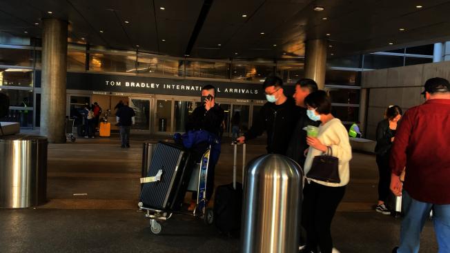 洛杉磯機場B號航站樓隨處可見帶著口罩推著行李走出海關口的華裔乘客(記者李雪/攝影)
