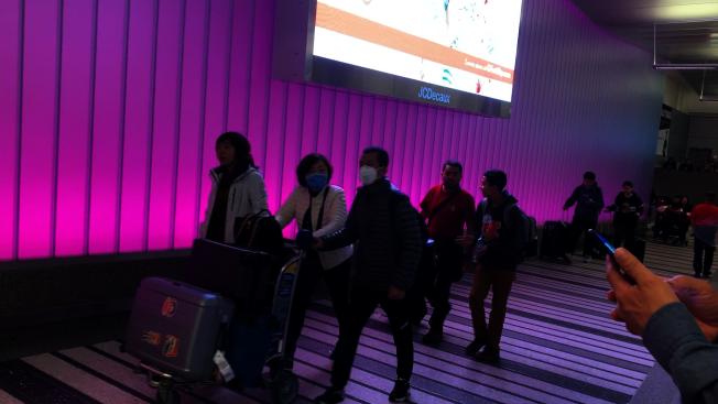 洛杉磯機場B號航站樓隨處可見到不少帶著口罩推著行李走出海關口的華裔乘客(記者李雪/攝影)