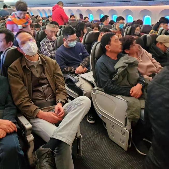 在飛往洛杉磯航班密閉的機艙裡,乘客們都謹慎地戴著口罩。(讀者提供)