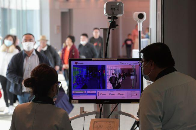 圖為新加坡衛生官員在樟宜國際機場入境時使用熱掃描儀篩查。Getty Images