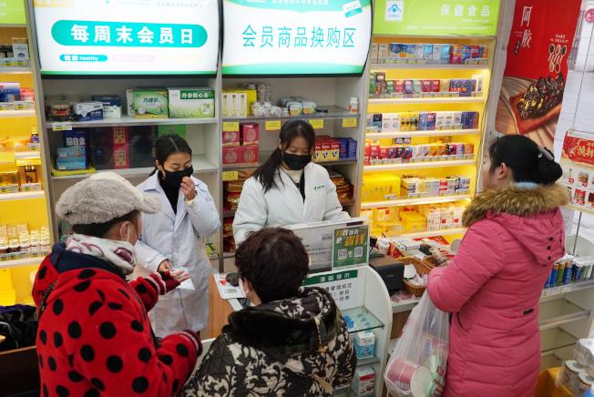 圖為武漢民眾23日在藥房採購各種防疫商品。美聯社