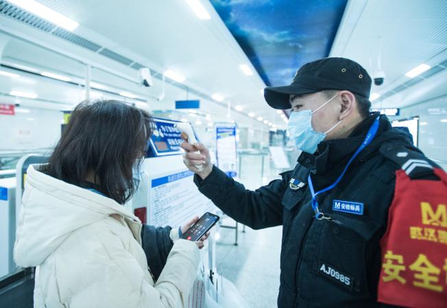 武漢封城防疫前,工作人員對地鐵乘客進行體溫檢測。(新華社)