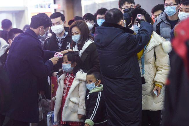 封城之前從武漢開出的一班列車23日抵達杭州,杭州火車站工作人員為每一個旅客量體溫。(Getty Images)