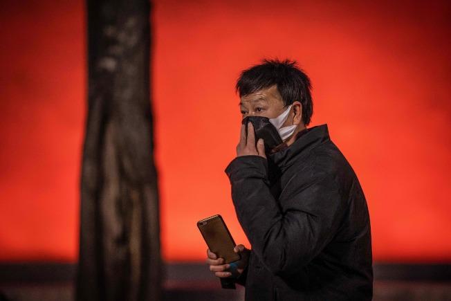 圖為北京民眾出門戴口罩自保。(Getty Images)