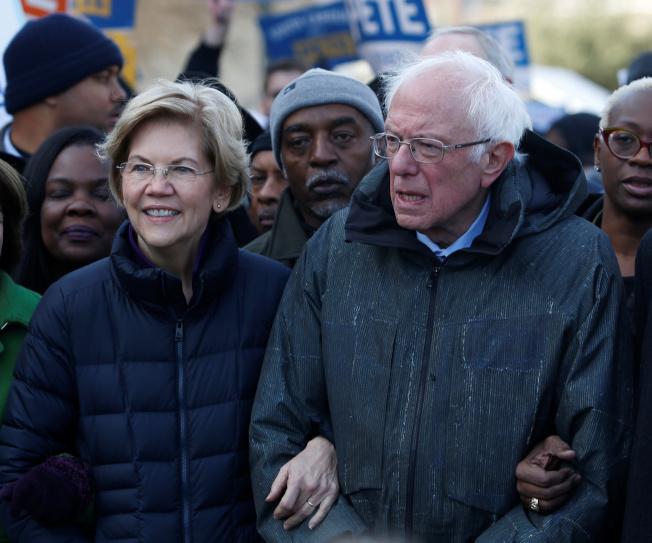 民主黨總統提名參選人華倫(左)和桑德斯手挽手在南卡州首府哥倫布參加金恩日遊行。(路透)