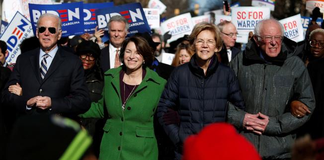 民主黨總統提名參選人白登(左起)、柯洛布查、華倫及桑德斯手挽手參加金恩日遊行。(路透)