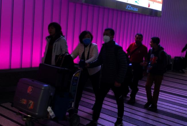 22日走出LAX航站樓的華裔乘客,不少都佩戴口罩防護。(記者李雪/攝影)