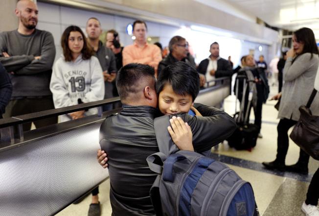 親子分開一年半後,瓜地馬拉移民索爾重返美國,在洛杉磯機場擁抱兒子。(美聯社)