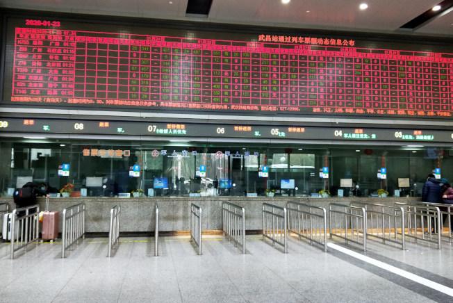 武漢暫時關閉機場、火車站離漢通道,圖為武昌火車站售票大廳內辦理退票的乘客。(中新社)