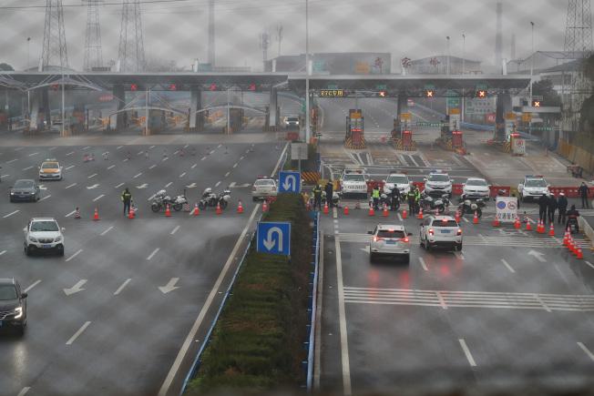 為防止疫情擴散,湖北多處高速公路口封閉,圖為警方23日在武漢市洪山區武鄂高速公路進行交通管制。(中新社)