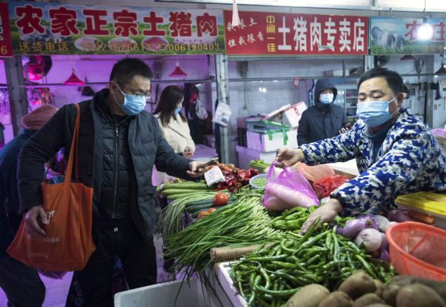 武漢封城防疫,1100萬市民暫時被隔離在市內,居民照樣在菜市場買菜準備過年。(美聯社)