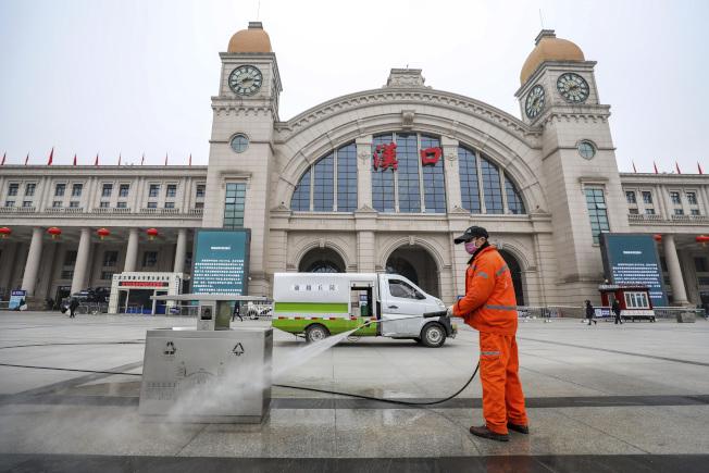 圖為防疫人員正在漢口火車站外清洗地面。(美聯社)
