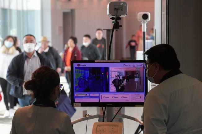 圖為新加坡衛生官員在樟宜國際機場入境時使用熱掃描儀篩查。(Getty Images)