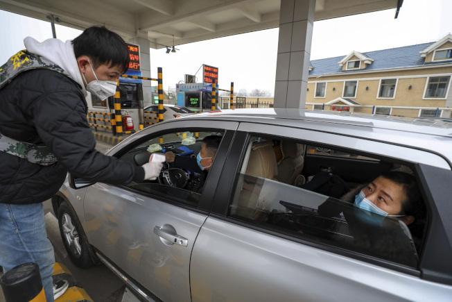 武漢肺炎疫情令灣區留學生擔心家人。圖為武漢一個公路收費口工作人員測量過往車輛人員體溫。(美聯社)