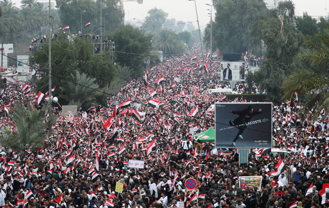 伊拉克民眾24日在巴格達街頭舉行大規模示威,要求美軍撤離。(路透)