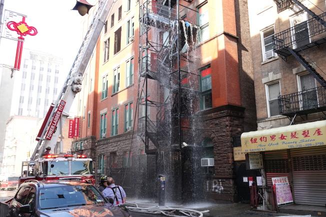 24日下午火災現場仍駐紮著多輛消防車。(記者金春香/攝影)