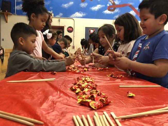 蒙特利公園市Bella Vista小學孩子們,用筷子夾糖果遊戲。(記者王若然/攝影)