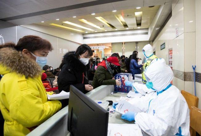 中國多個省市陸續出現新型冠狀病毒肺炎的感染個案,不少醫護人員疲於奔命;圖為武漢醫院的醫護人員接待求診者。(中新社)
