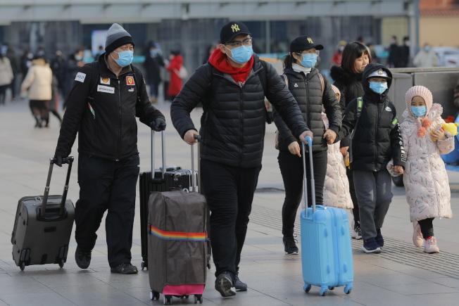 許多戴著口罩的旅客自北京火車站返回家鄉過年。(歐新社)