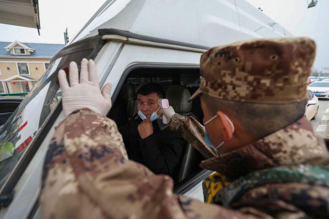 中國湖北省封城防疫的範圍擴大,圖為一名執法人員在高速公路檢查司機的體溫。(Getty Images)