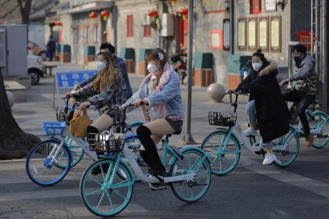 由於新型冠狀病毒肺炎疫情爆發,北京因此取消廟會等春節慶典。圖為北京民眾戴著口罩騎著腳踏車逛景山公園。(歐新社)
