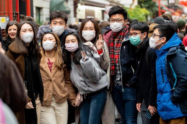 在倫敦的華埠,一眾留學生戴上口罩拍照。(Getty Images)