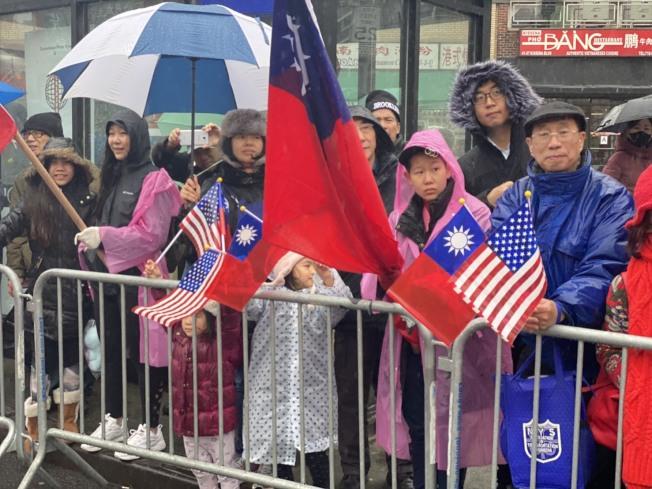民眾在街邊拿著國旗歡迎遊行隊伍。(記者牟蘭/攝影)