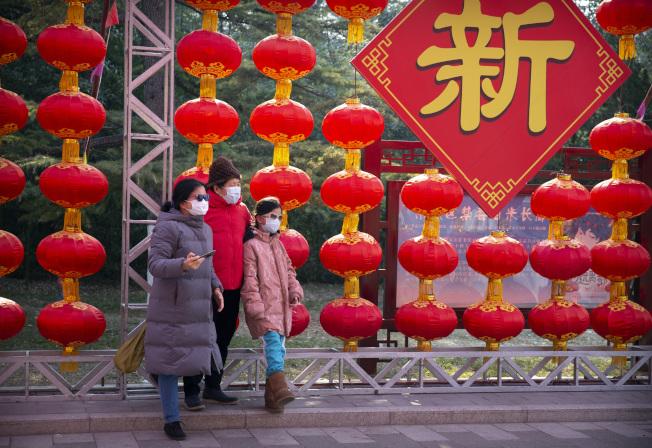 北京大年初一的街頭,民眾戴著口罩出門慶賀新年。(美聯社)