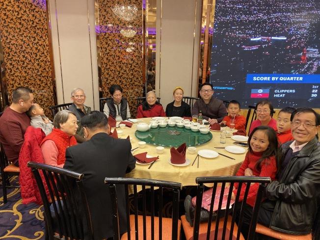 譚先生(右一)閤家祖孫三代14口在餐館吃年夜飯。(記者謝雨珊/攝影)