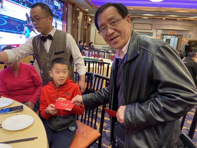 譚先生在場發紅包給孫子。(記者謝雨珊/攝影)